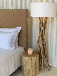 Cama com uma mesa de cabeceira do seu lado direito, uma vela em cima da mesa de cabeceira e um candeeiro
