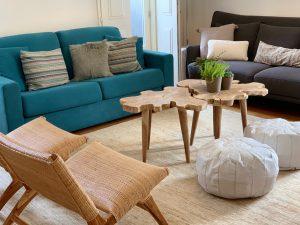 Sala com um sofá grande azul, um sofá cinzento à esquerda e uma mesa de centro de madeira