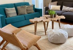 Sala com um sofá grande azul turquesa, sofá cinzento e mesa de centro de madeira.